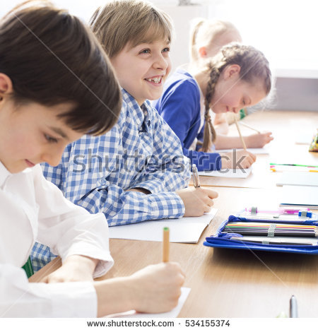 stock-photo-happy-hard-working-kids-writing-an-exam-in-primary-school-534155374